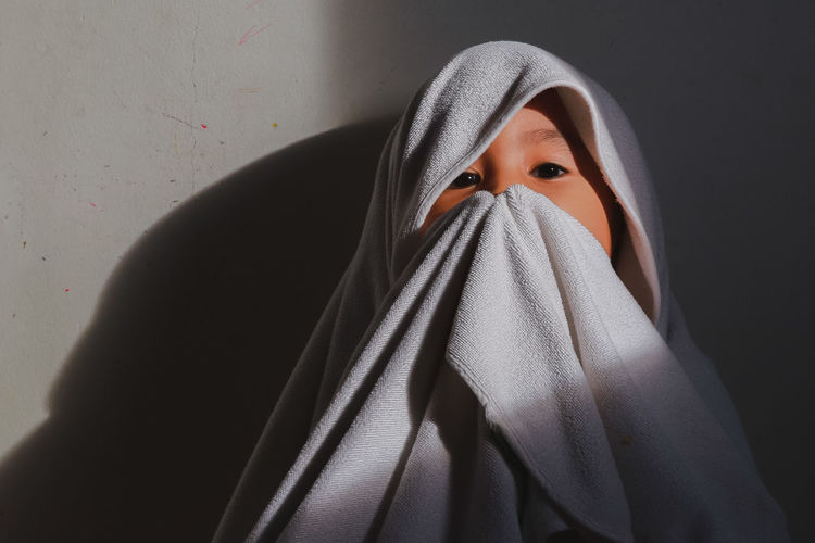 Portrait of boy wrapped in towel against wall