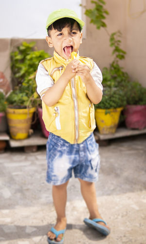 Full length portrait of boy holding yellow while standing outdoors