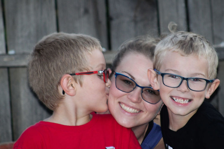 Portrait of smiling mother with sons against fence