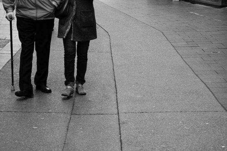 Low section of couple walking on sidewalk