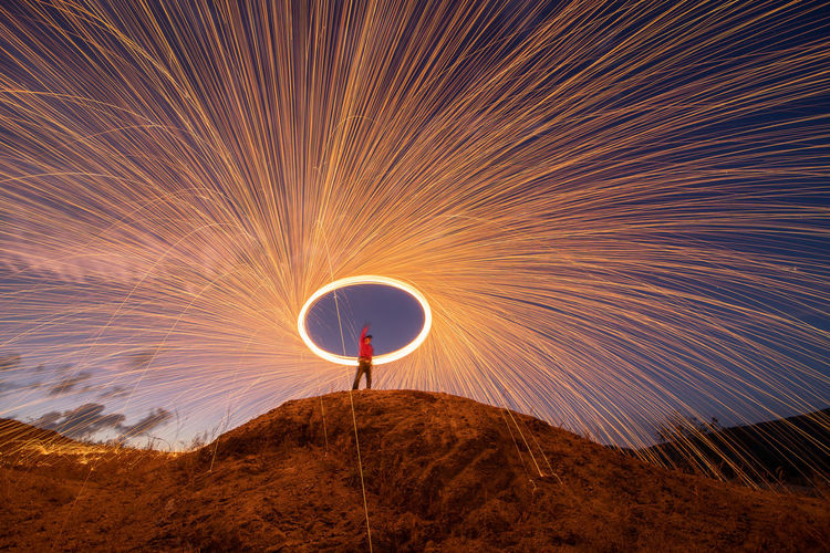 Low angle view of man spinning wire wool while standing on mountain against sky