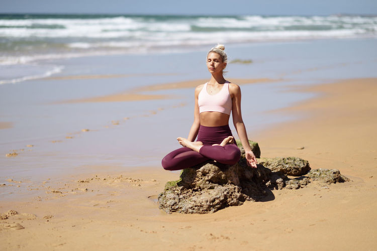 Caucasian woman practicing yoga at seashore. Young female doing lotus pose in the beach in Cadiz, Andalusia, Spain. Beach Land Water One Person Sea Lifestyles Full Length Day Sand Nature Beauty In Nature Leisure Activity Real People Women Young Adult Smiling Sitting Outdoors Beautiful Woman