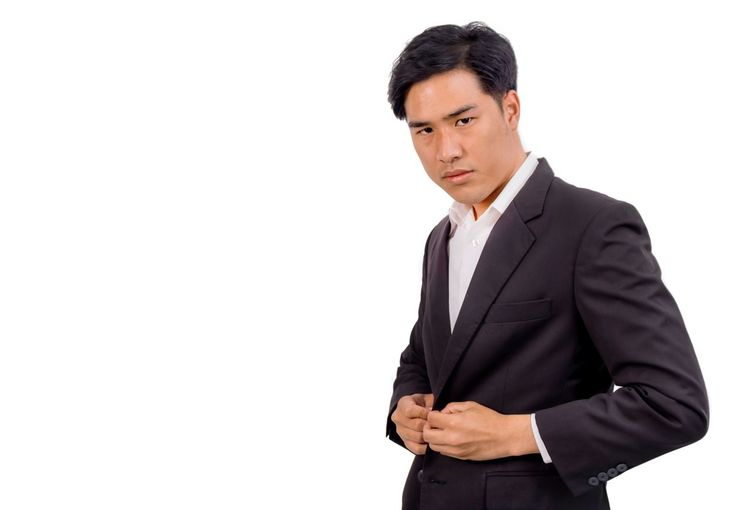 An Asian man is nervous while putting on his black suite. One Man Only Businessman White Background Business Only Men Studio Shot Professional Occupation One Person Cut Out Men Copy Space Adults Only Well-dressed Suit Males  Business Person Adult Occupation People White Collar Worker Nervous Man Handsome Man Confused Face Asian Man Asian Worker