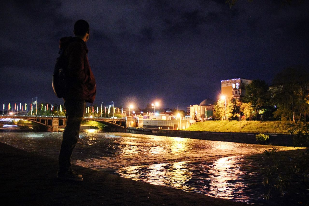 night, water, illuminated, architecture, built structure, building exterior, sky, nature, city, real people, full length, reflection, standing, men, one person, river, lifestyles, rear view, outdoors