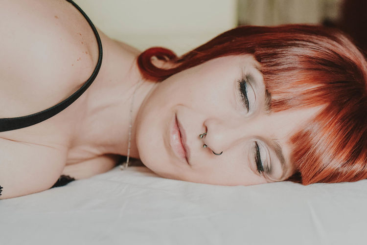 Close-up of young woman lying on bed