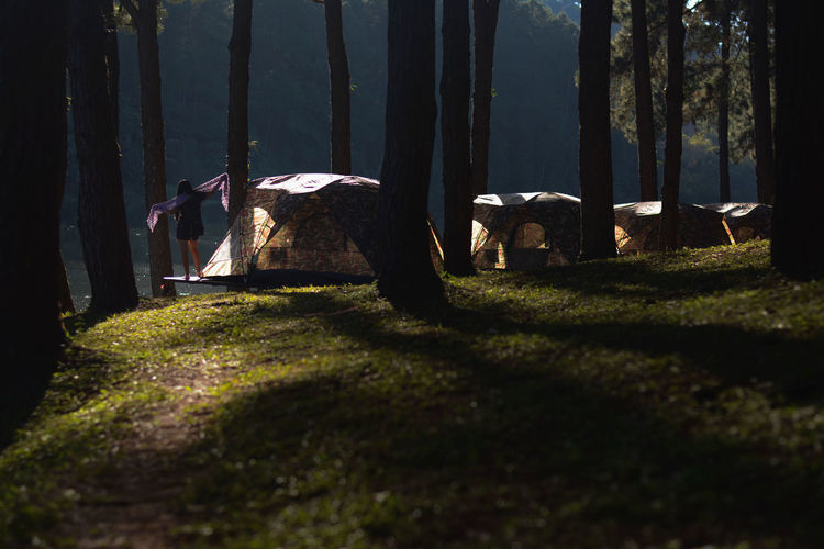 Woman With Arms Outstretched Standing By Tent In Forest