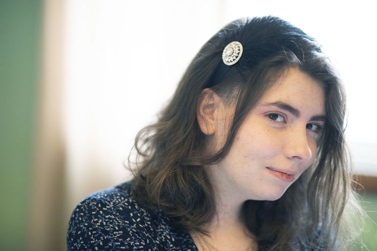 A 20-year-old woman sits for a portrait. Headshot Portrait One Person Young Adult Hair Beautiful Woman Hairstyle Long Hair Contemplation Focus On Foreground Indoors  Lifestyles Young Women Real People Beauty Close-up Front View Looking Away Pretty Girl Headband Canon Brunette Looking At Camera