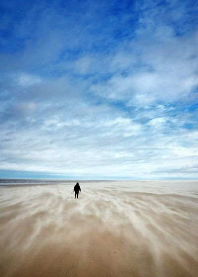 Rear view of man walking at beach against sky during winter