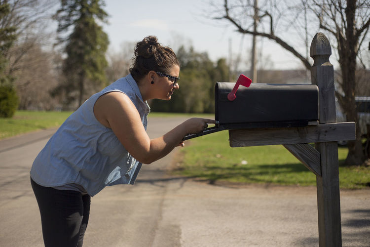 Side view of young woman standing by mailbox on street against sky