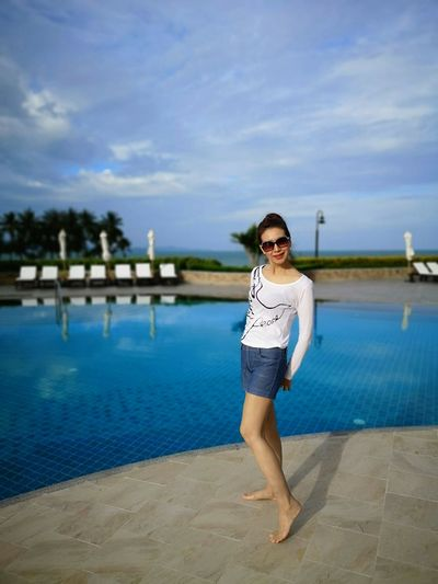 Portrait of woman standing at poolside against sky