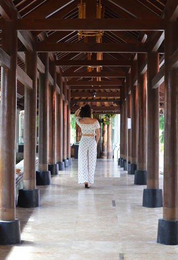 Asian lady walking down hallway with wooden column on sides