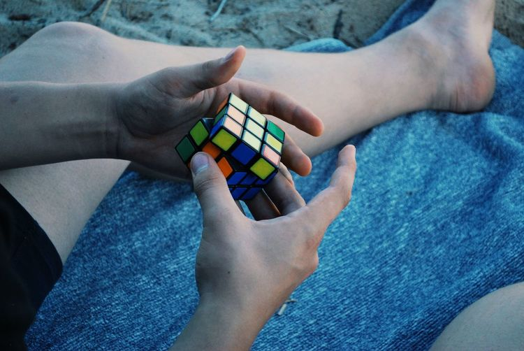 Low section of man holding puzzle cube while sitting at beach