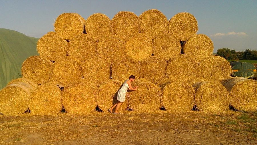 Full length of woman standing by hay bale on field