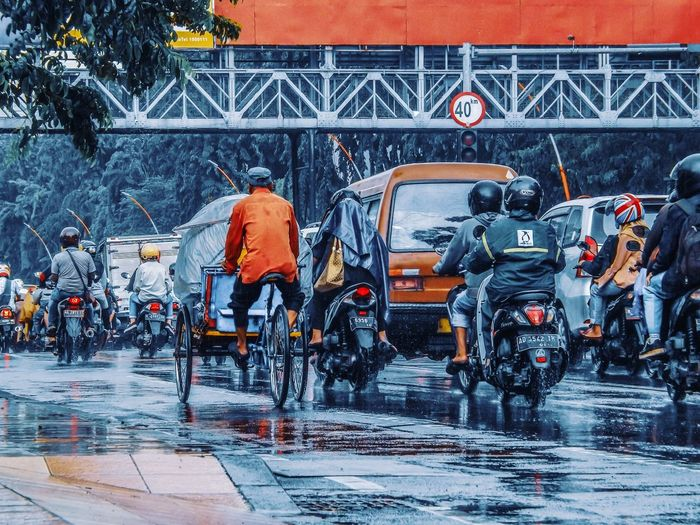 People Riding Vehicle On Wet Street In City During Rainy Season