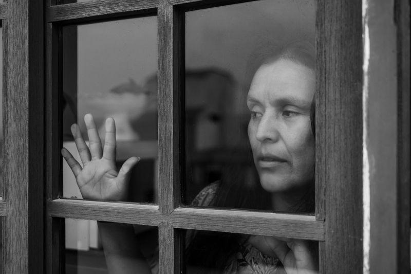Portrait of woman looking through window in building