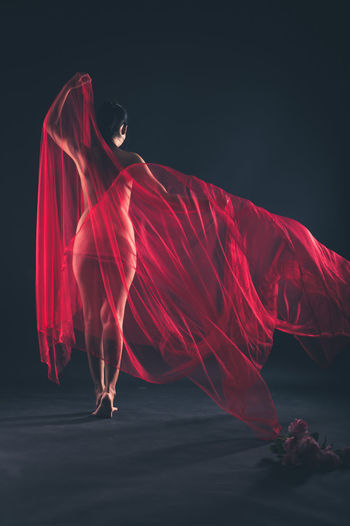 Full Length Of Naked Woman With Red Fabric Against Black Background
