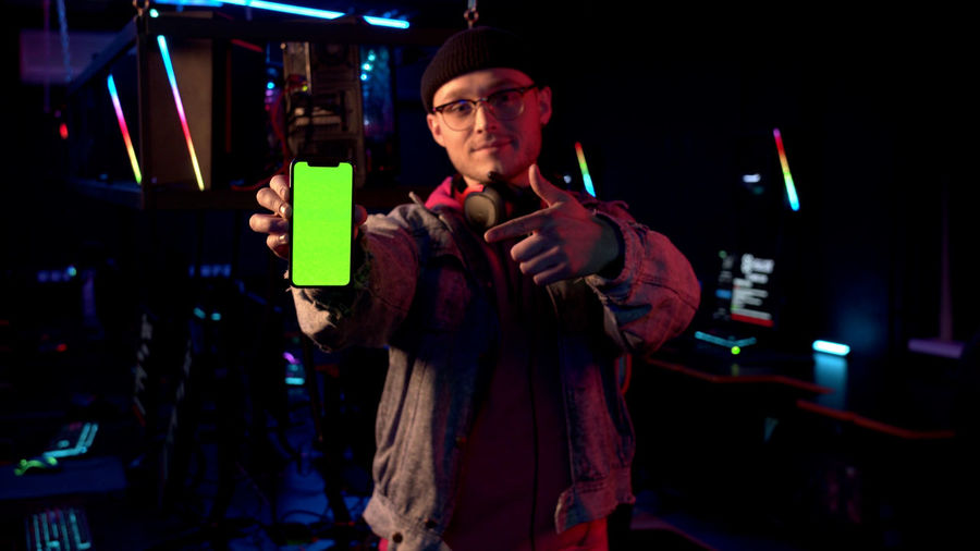 Portrait of man using mobile phone while sitting in darkroom