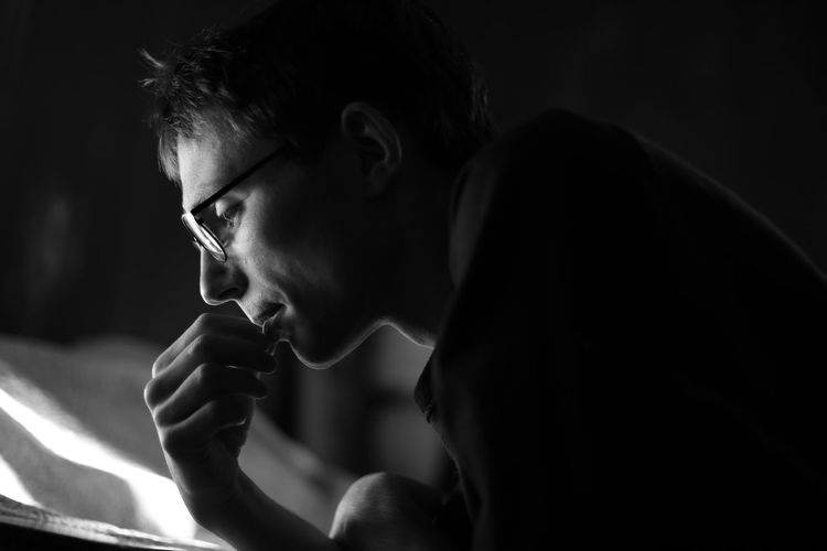 Side View Of Serious Young Man Reading Book In Dark Room