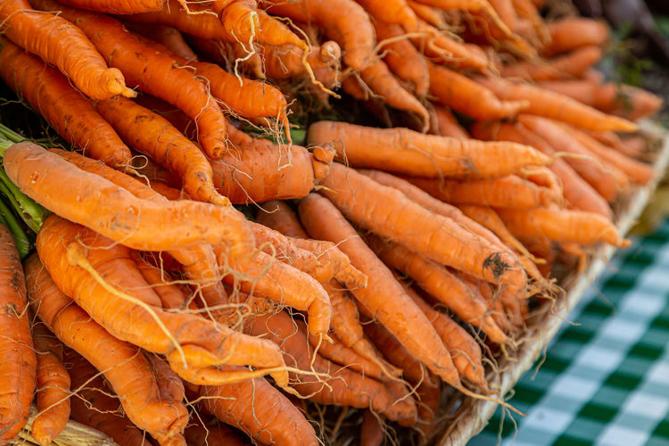 A display of carrots for sale on a farmers market stall