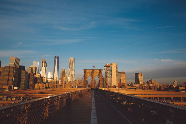 Brooklyn bridge in city against blue sky