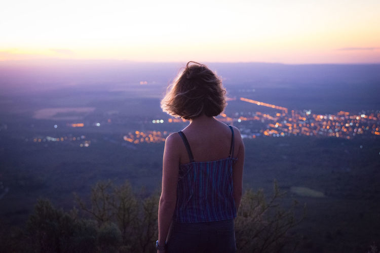 Rear View Of Woman Looking At Illuminated Cityscape Against Sky During Sunset