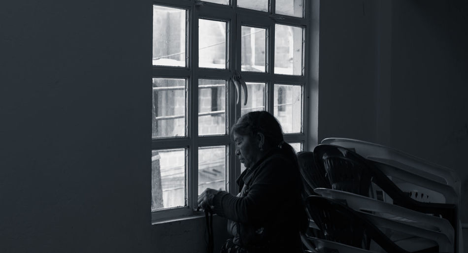 Window Real People One Person Indoors  Lifestyles Glass - Material Transparent Day Leisure Activity Standing Adult Sitting Home Interior Dark Waist Up Women Three Quarter Length Looking Through Window Contemplation Waiting