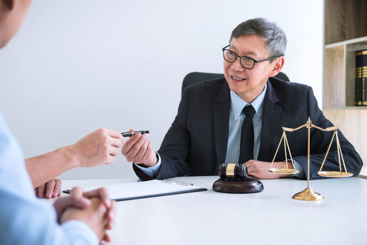 Lawyer Having Meeting With Clients In Courtroom