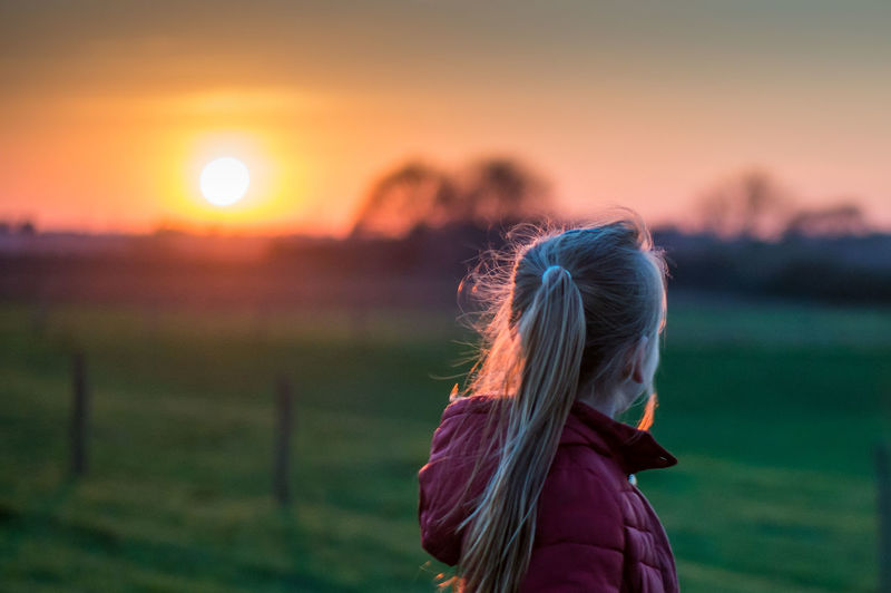 Rear view of girl wearing hooded jacket standing on grassy field during sunset