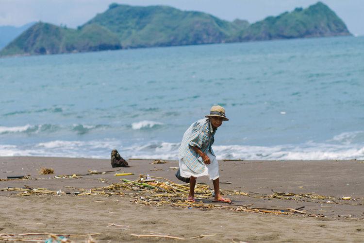 Senior woman picking drift wood at sea shore