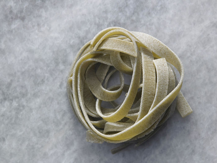 tagliatelle pasta Cooking Dried Food Food And Drink Noodles Shape Tagliatelle Textured  Wheat Carbohydrate - Food Type Close-up Directly Above Food Freshness High Angle View Indoors  Ingredient Italian Food No People Nutrition Pasta Product Raw Food Spiral Still Life Table