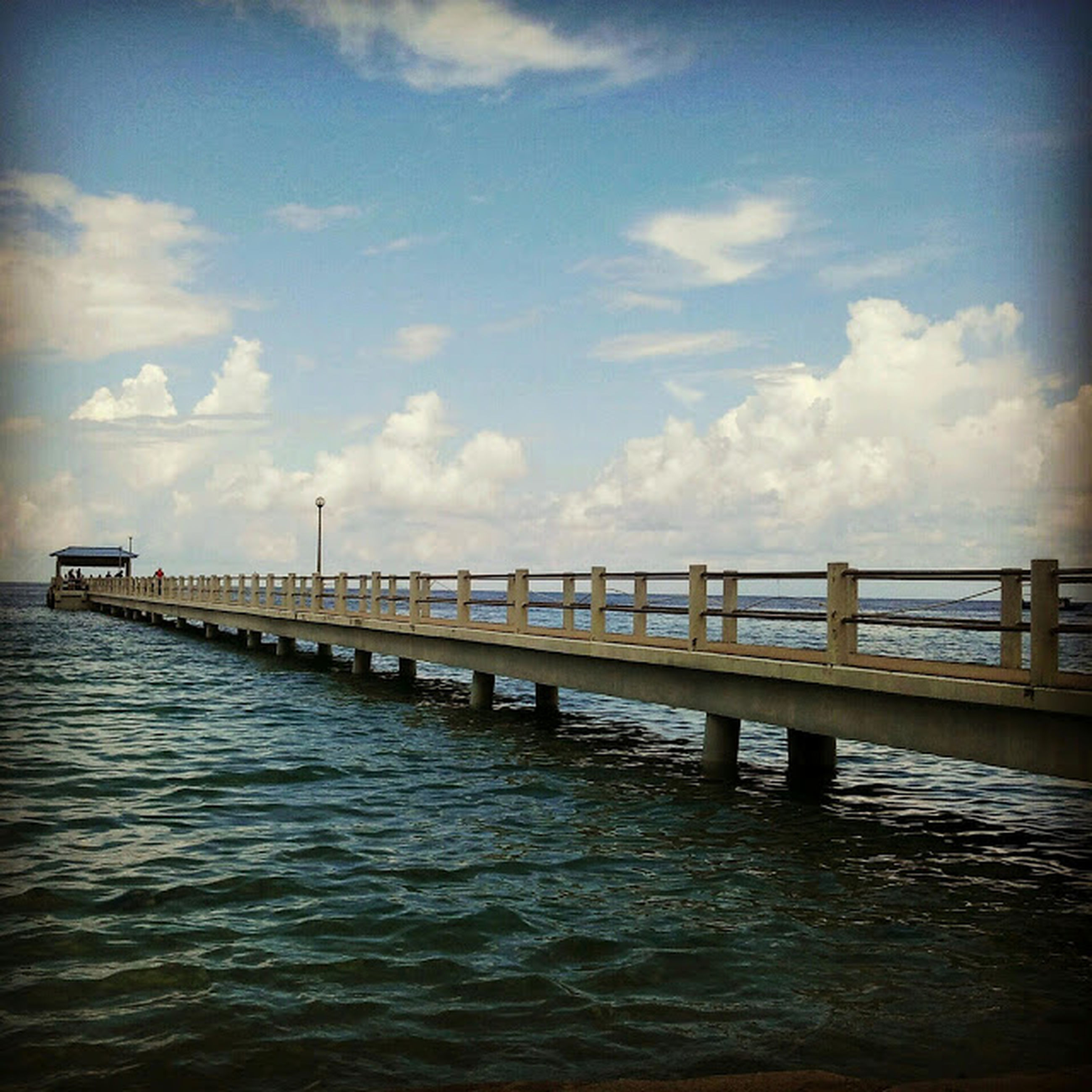 water, sea, sky, waterfront, pier, built structure, rippled, architecture, cloud - sky, tranquility, tranquil scene, nature, scenics, cloud, beauty in nature, connection, day, horizon over water, outdoors, blue