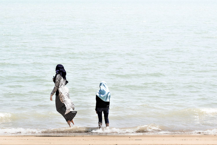 Rear view of girl standing by woman levitating on shore at beach