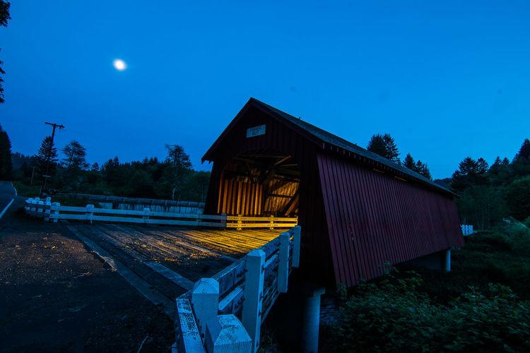 Covered footbridge against clear sky at dusk