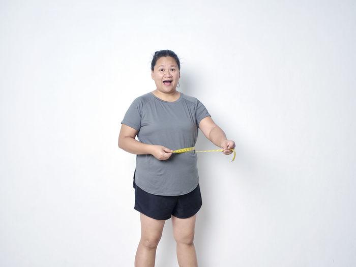 Full length portrait of happy girl standing against white background