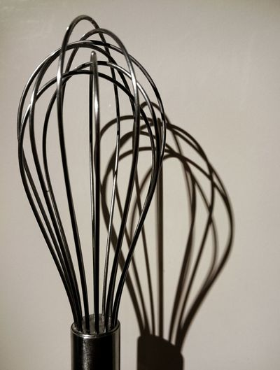 Close-up of wire whisk against wall