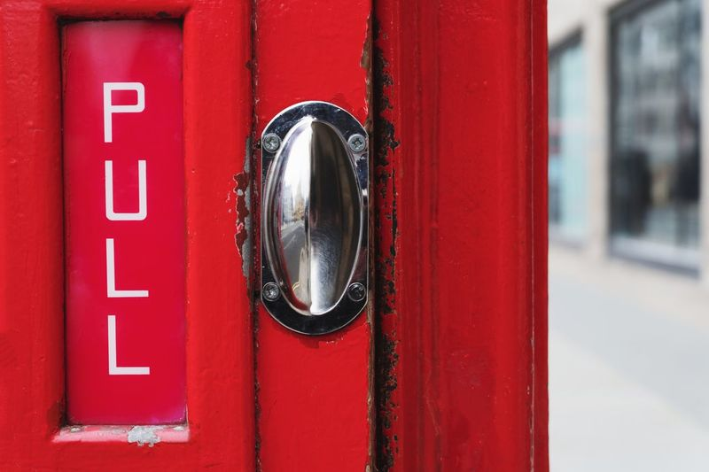 Pull - Handle on a red London phone box London Phonebox Phonebooth Handle Pull Red Focus On Foreground Close-up Communication Entrance Door Day No People Metal Outdoors City Text