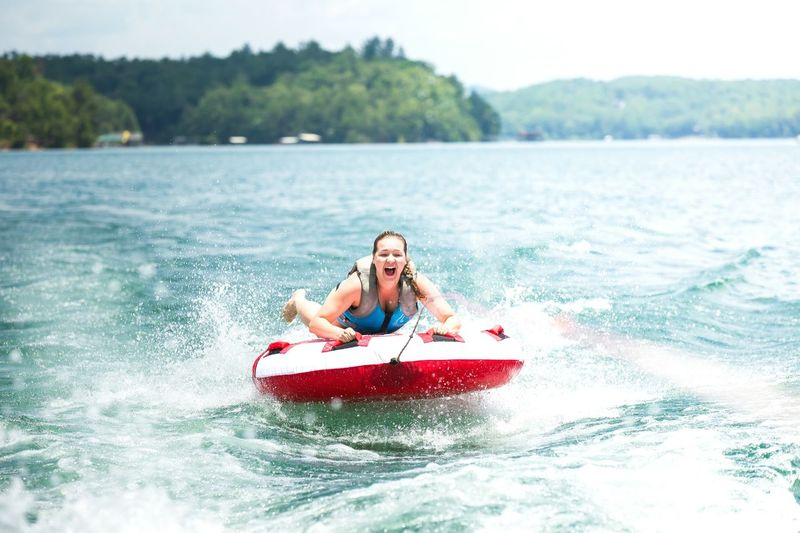 Young Woman On Inflatable Raft Pulled By Speedboat In Lake Blue Ridge