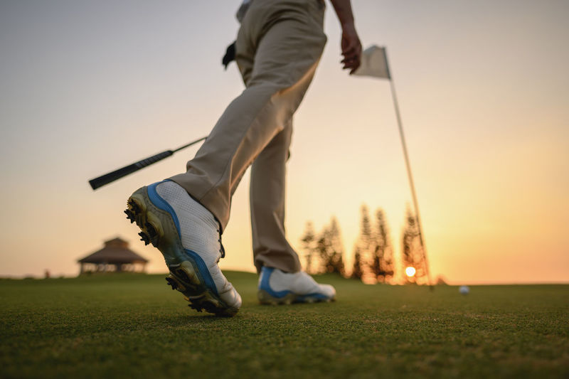 Low section of men on golf course against sky during sunset
