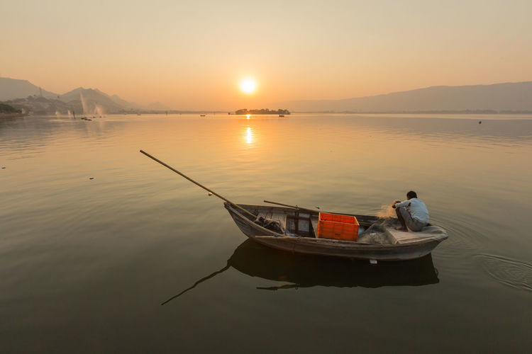 Side view of man traveling in boat on sea against sky during sunset