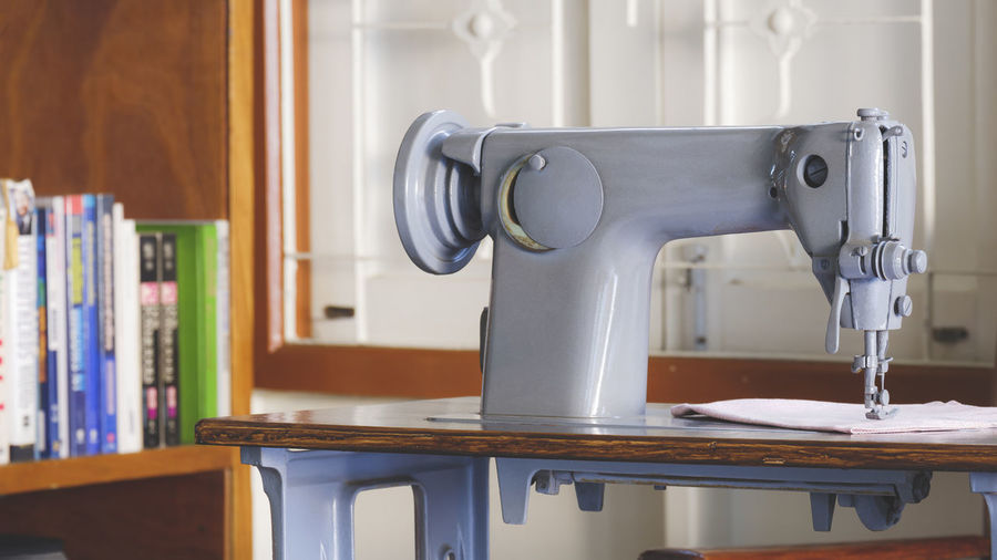 Close-up of sewing machine on table at home
