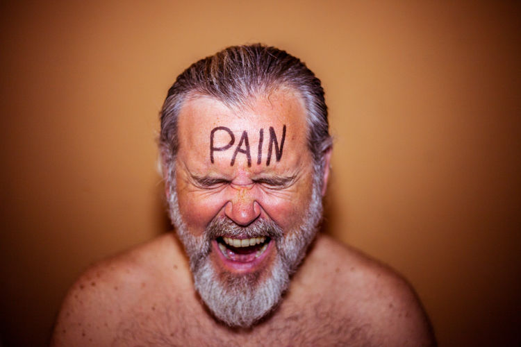 Shirtless man with pain text on forehead against brown background