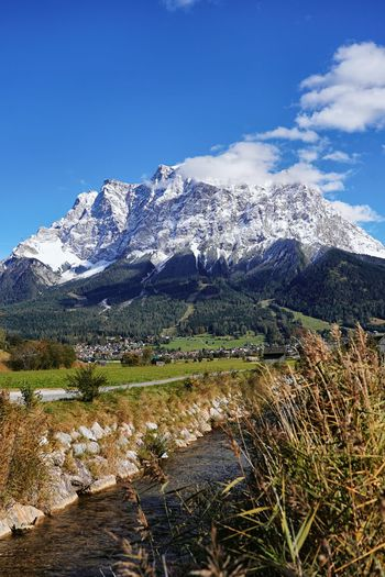 Scenic view of snowcapped zugspitze mountain against blue sky