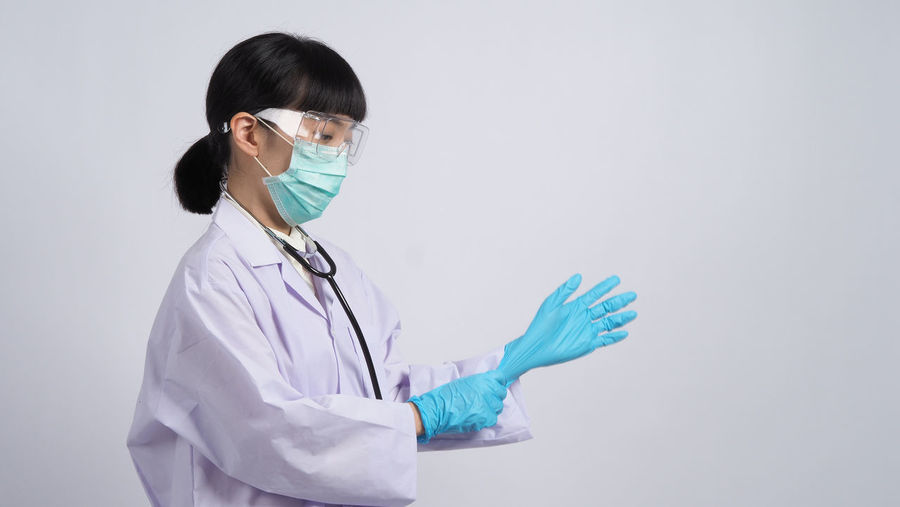 Young woman wearing mask against white background
