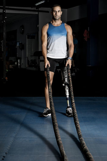 Full Length Of Determined Disabled Man Exercising With Battle Ropes At Gym
