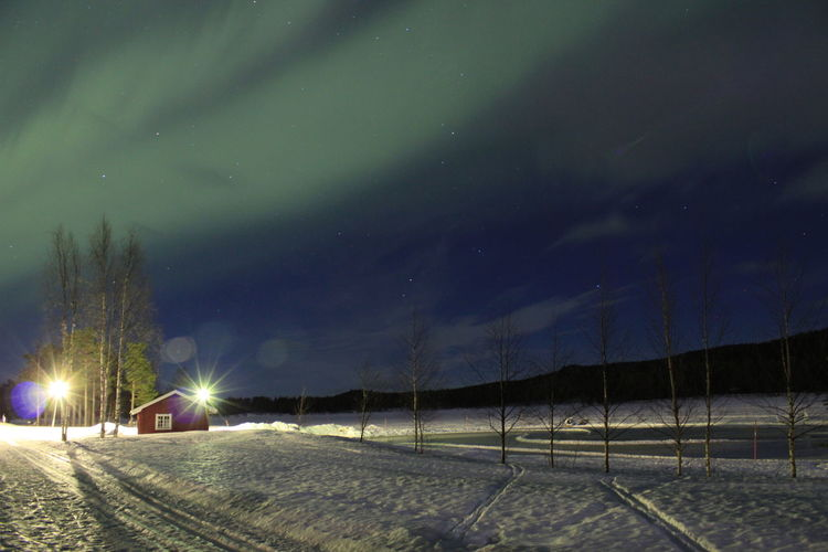 House on snow covered field against sky at night