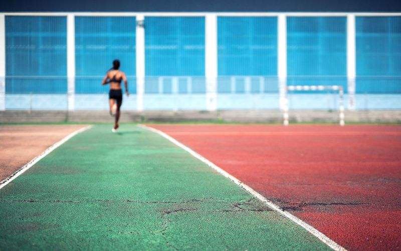 Rear view of female athlete running on sports track