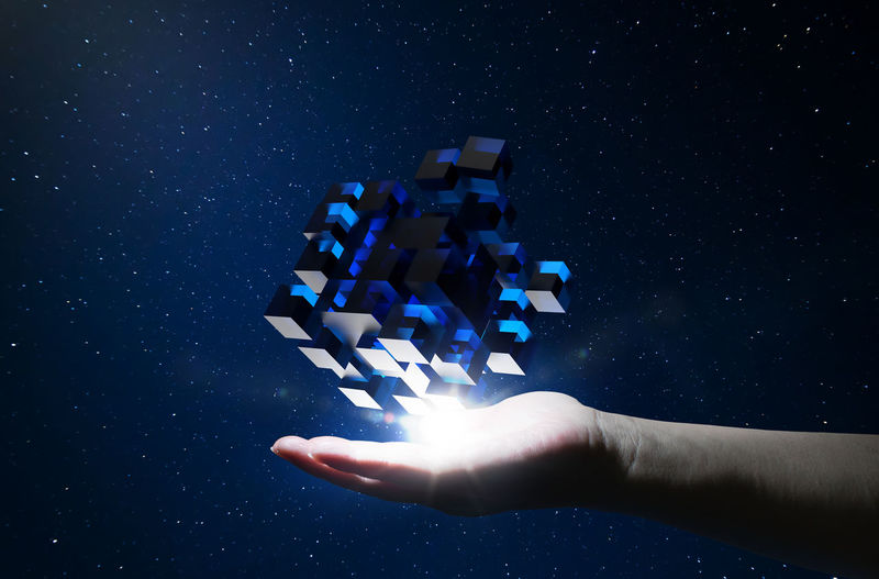 Digital composite image of woman touching cube shaped box in space