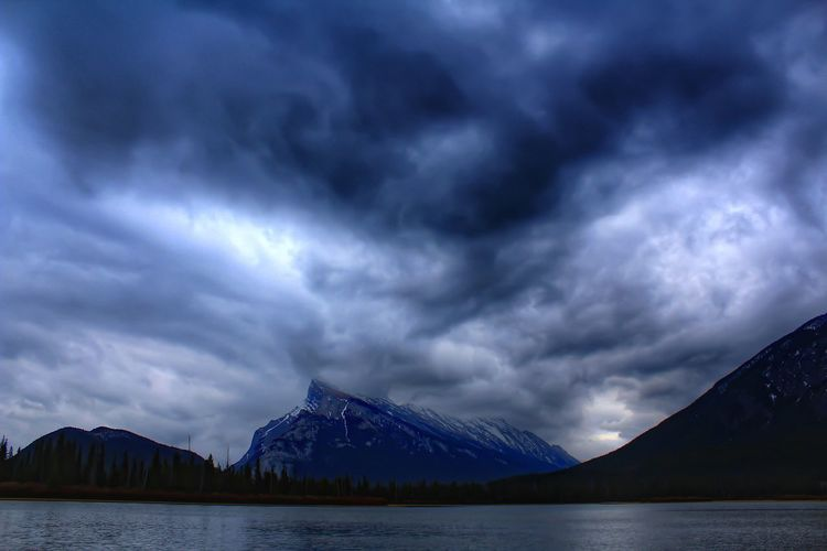 Scenic view of mt rundle by lake against cloudy sky