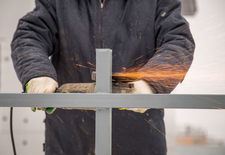 Midsection of man cutting metal in factory