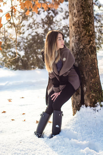 Full length of smiling woman on tree trunk during winter